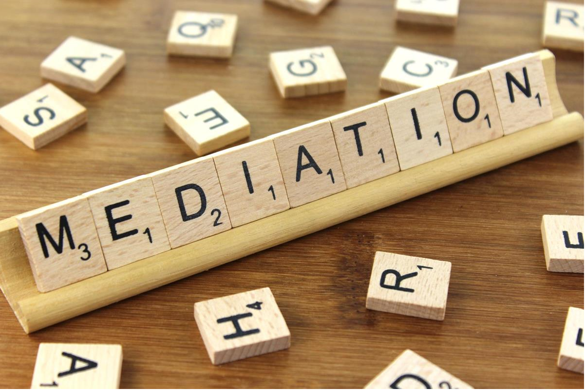 Scabble letter spelling out 'Mediation' with other letters scattered around