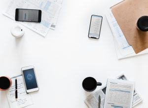 A birds eye view of a meeting desk with papers and phones