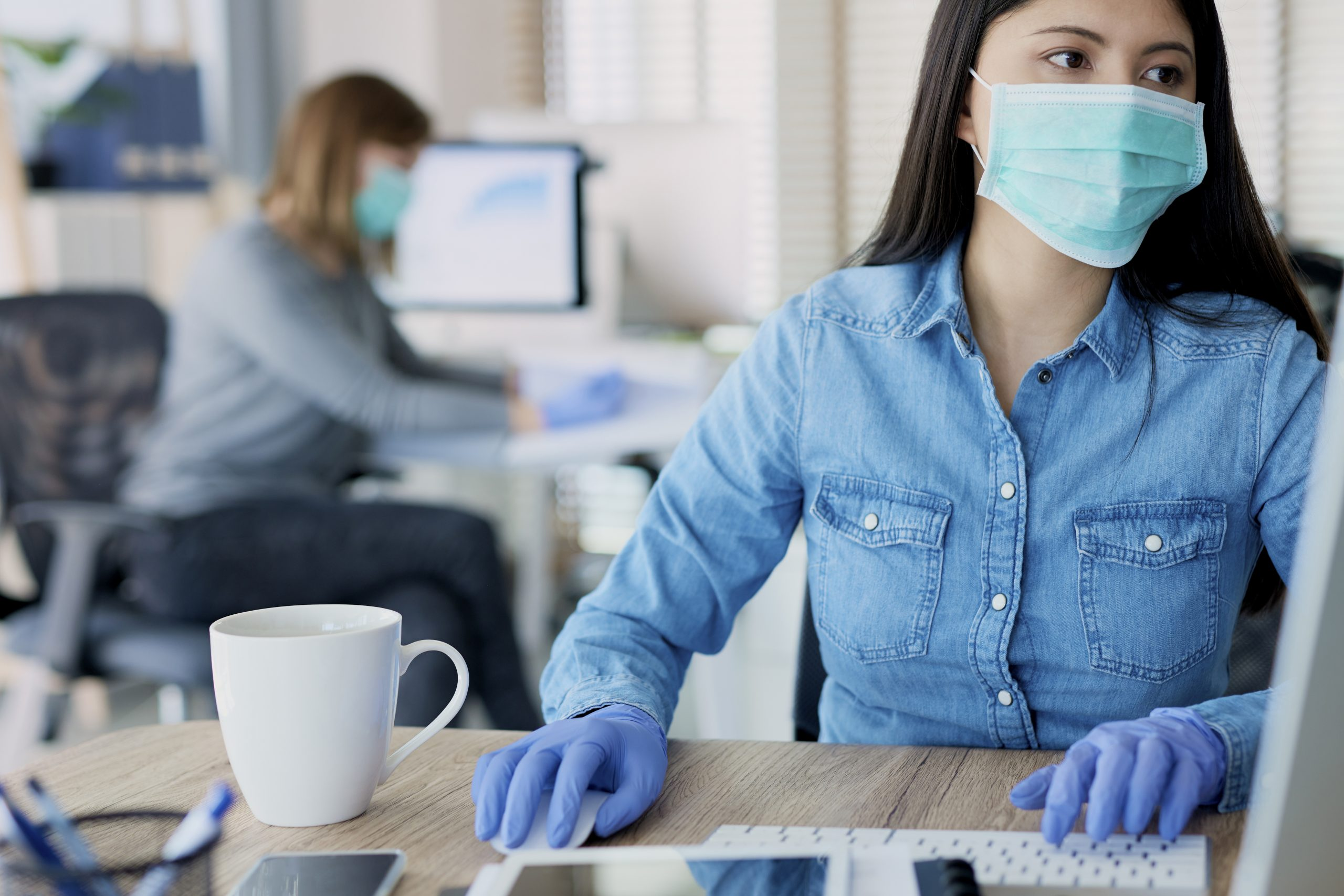 Office worker wearing PPE including gloves and facemask