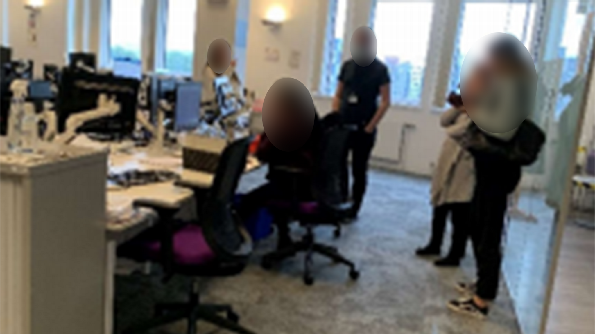 Photo of a workplace with staff congregating around a desk