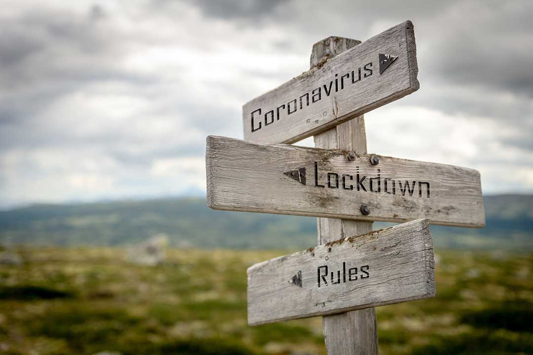 A wooden sign post with three arrows, they say, Coronavirus, Lockdown and Rules.