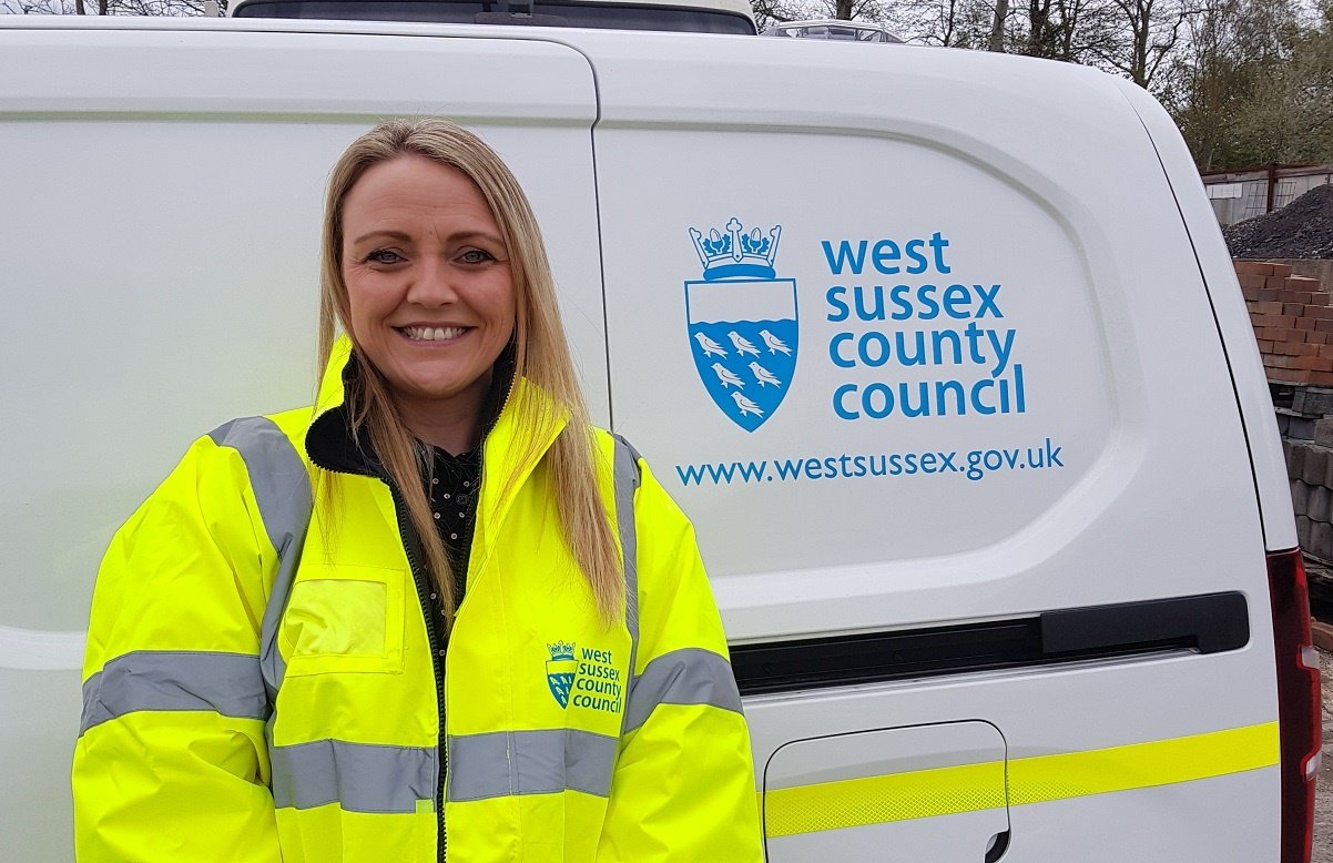Photo of Karla Overington wearing a West Sussex County Council jacket, stood in from of a West Sussex County Council branded van