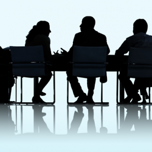 A silhouette of people sat around a meeting table